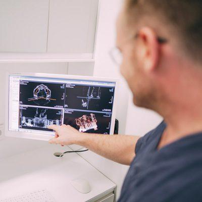 Dr. Thorn zeigt auf einem Bildschirm die idealen Stellen für Zahnimplantate.