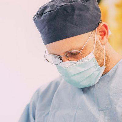 Dr. Thorn konzentriert sich, während er einem Patienten Zahnimplantate einsetzt