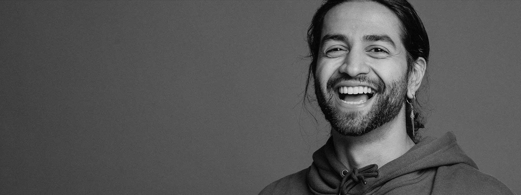 Mann mit gesunden und schönen Zähnen lacht, weil es ihm beim Zahnarzt in Frankfurt gut gefällt.