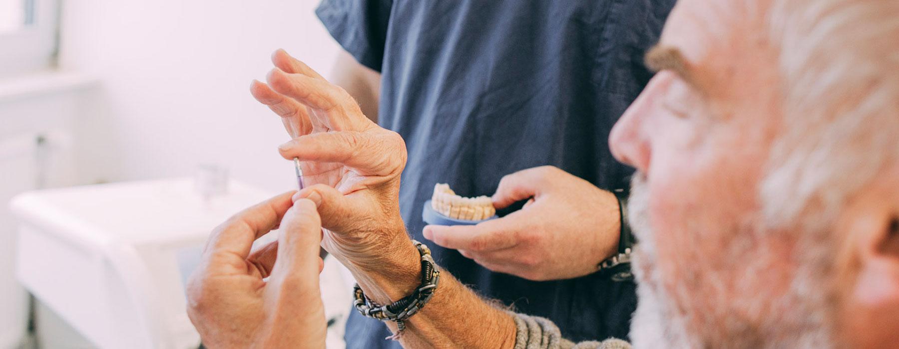 Patient hält kleines Zahnimplantat zwischen den Fingern, das ihm Dr. Thorn in Frankfurt einsetzen möchte.