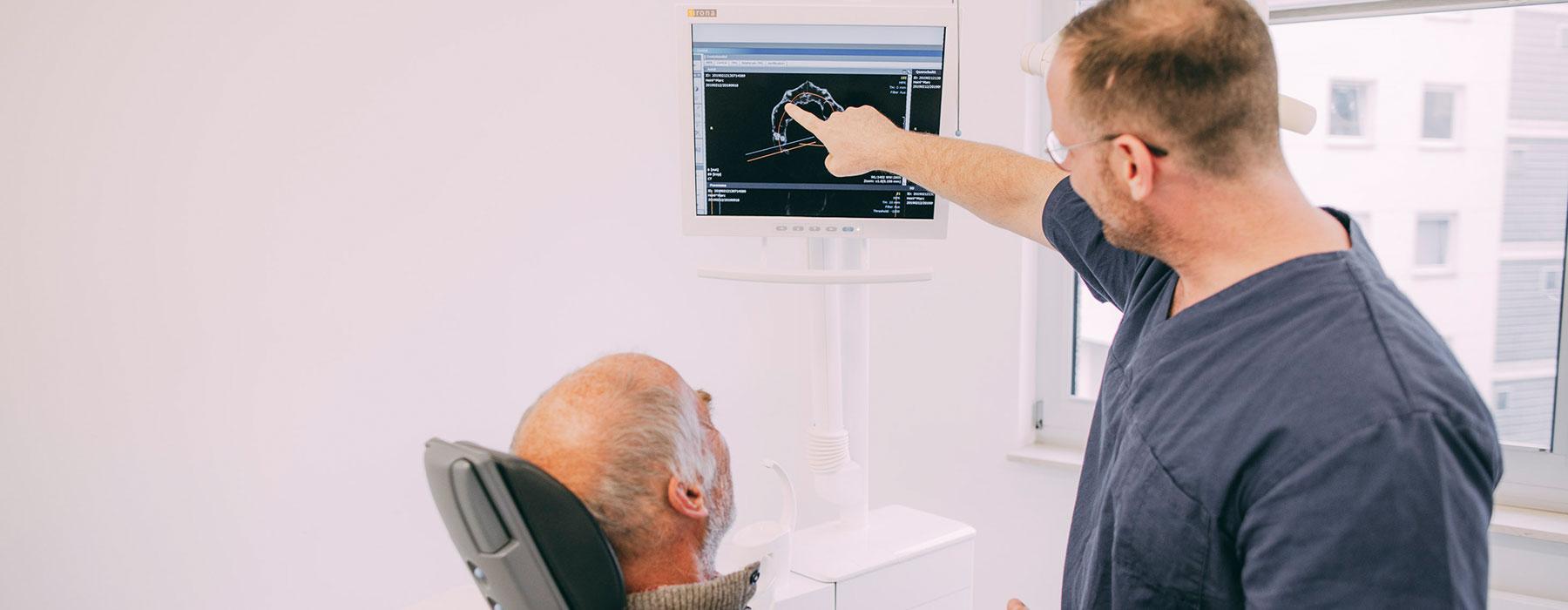Dr. Thorn zeigt Patienten, an welchen Stellen er Zahnimplantate setzen möchte.