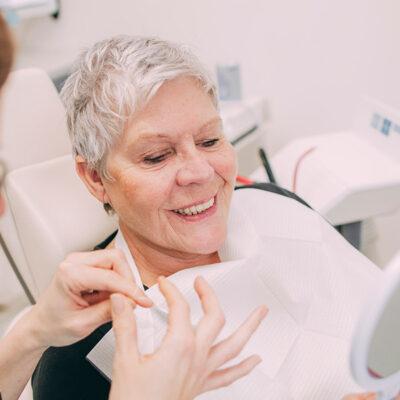 Frau sitzt zur Behandlung für Zahnästhetik beim Zahnarzt in Frankfurt.