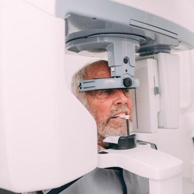 Patient steht zur Röntgenaufnahme in einem DVT beim Zahnarzt in Frankfurt