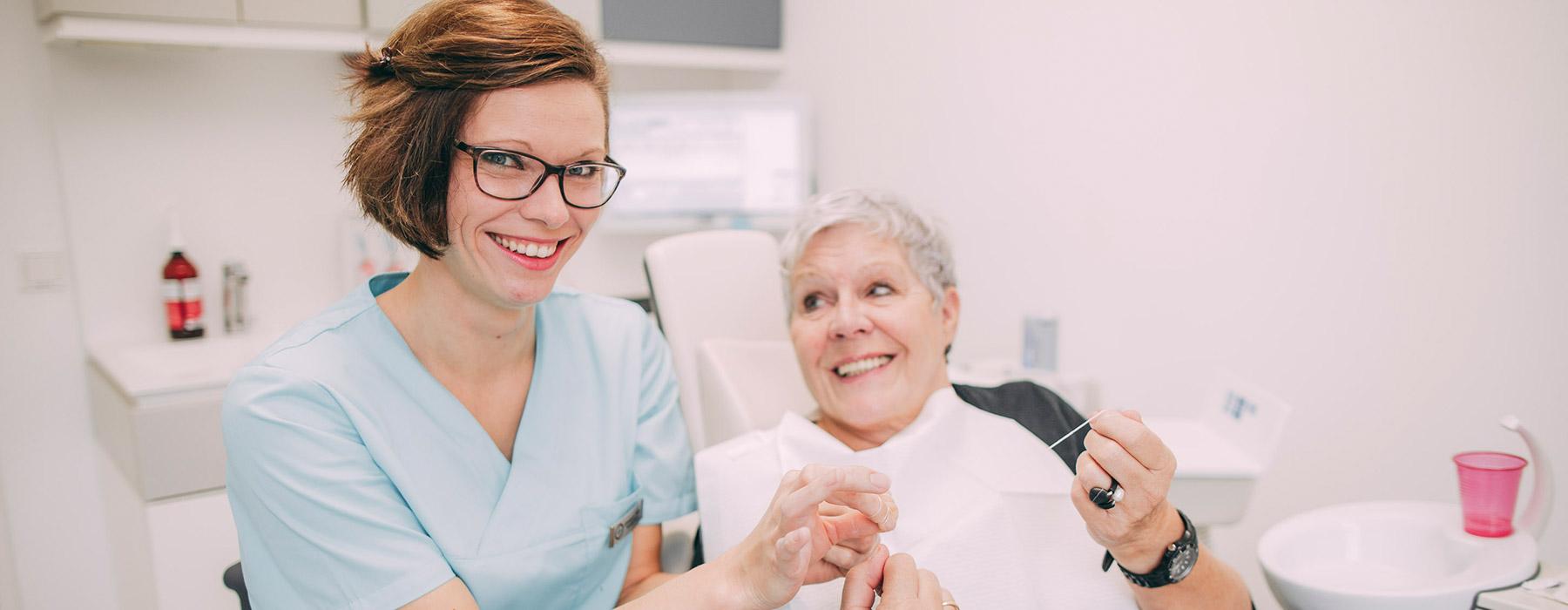 Mitarbeiterin und Patientin freuen sich über gelungene Zahnprophylaxe in Frankfurt