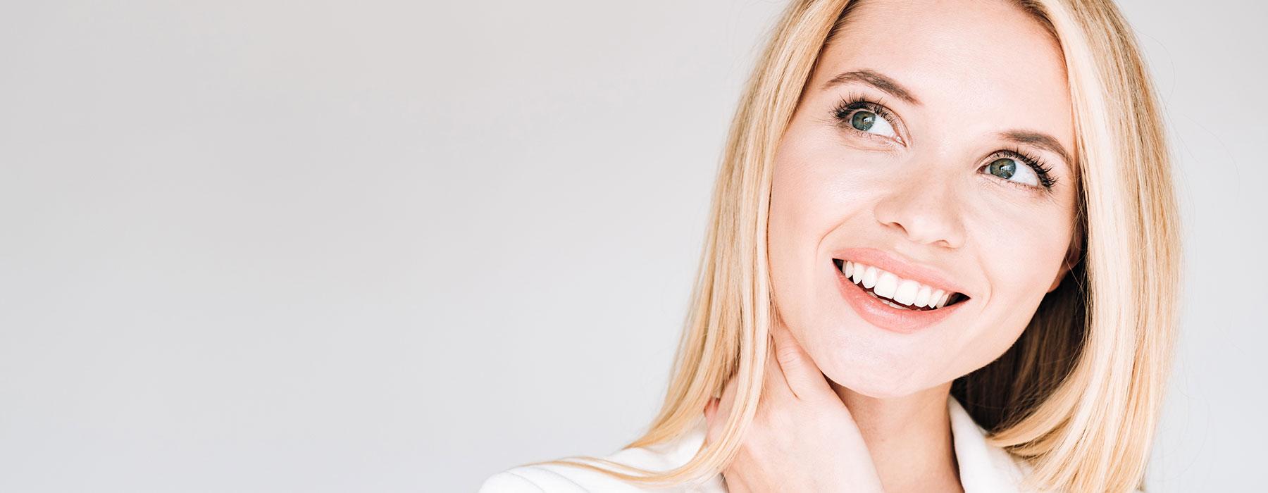 Frau lacht dank Zahn-Veneers aus Frankfurt mit schönen Zähnen.